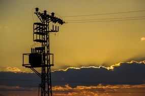 high-voltage tower on a background of golden sunset