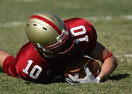 American Football player with the ball is lying on the lawn