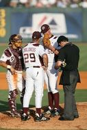 texas baseball team players with coach discuss strategy