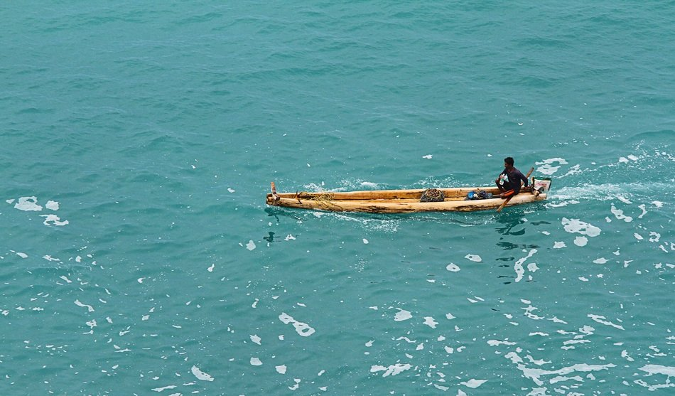 dark skin man in wooden fishing boat on sea