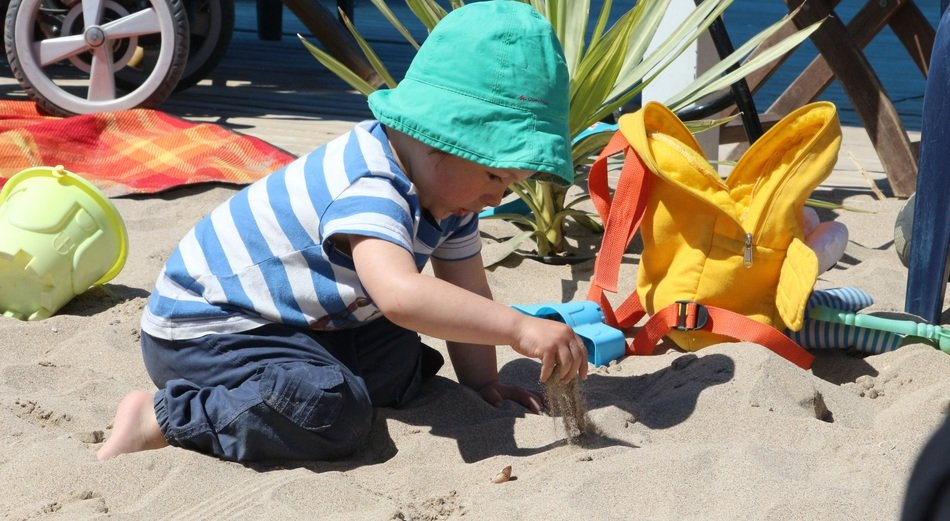 Child boy in colorful clothing Plays with Sand on Beach