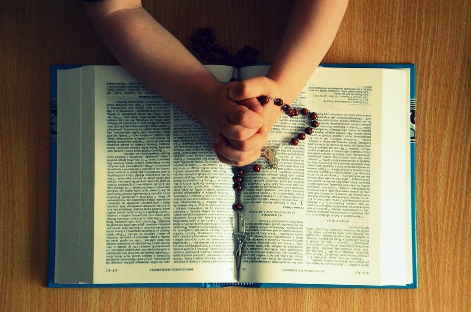 Praying person's hands with Rosary on open Bible