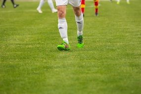 soccer player in green sneakers on the field