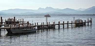 boats near a wooden pier on lake chiemsee