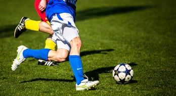 photo of soccer players legs and ball on the lawn