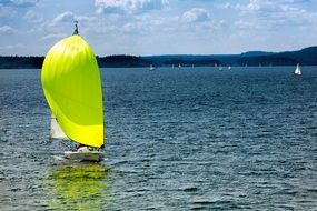 boat with a bright green sail on the lake
