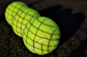 three green tennis balls close up