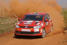 red racing car on a dusty rally track in india