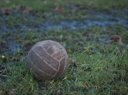 worn ball on green grass