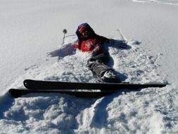 skier lies in the snow on the slope