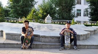 two young skateboarders on a city street