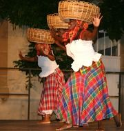 African dancers hold baskets on their heads in the Caribbean
