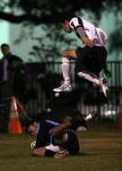 soccer player jumps over a player