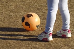 child stands near an inflatable ball