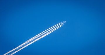 White trails of the airplane in blue sky