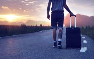 young man with a suitcase goes on the road