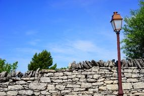 Street lamps near a stone wall