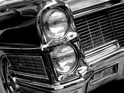 black and white photo of headlights cadillac