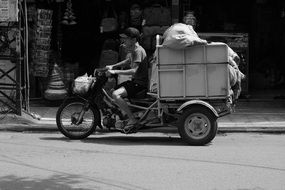 Black and white photo of the man with the moped in Vietnam