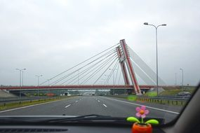 suspension bridge across Highway, view from the car
