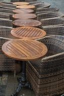 wicker chairs and wooden table in a street cafe bistro