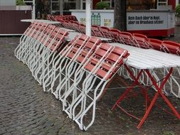 folded chairs of a street cafe in the rain
