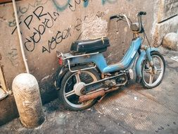 old dirty moped near the wall