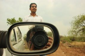reflection of the camera lens in the side mirror of the car