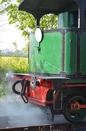 A couple near a steam locomotive on the railway