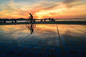 cyclist rides along the promenade in Zadar at sunset