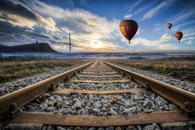 Hot Air Balloons in sunset Sky above railway
