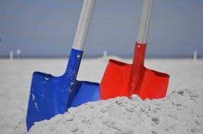red and blue shovels in the sand