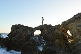 Man is climbing on the rocks near the ocean