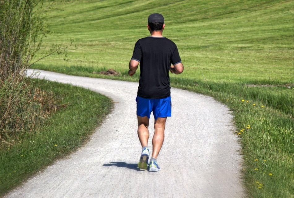 Jogger, man Running away on winding road at field