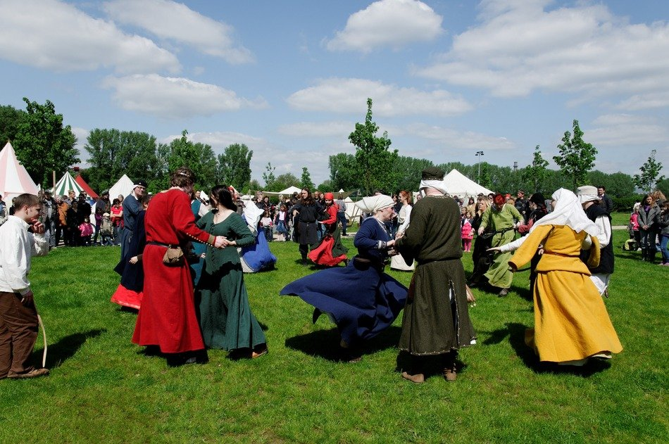 people in Medieval clothing Dancing on Meadow at market