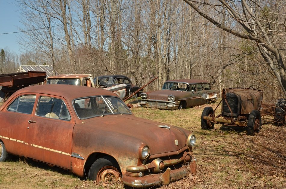 brown rusty cars in landfill