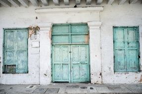 facade of an old building with turquoise doors