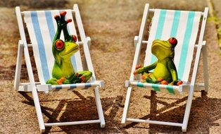 ceramic frogs relax on sunbeds