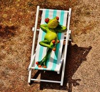 ceramic frog lies on a sunbed