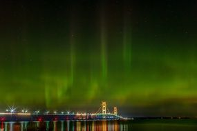 northern lights over a bright bridge in michigan