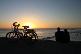 couple near bicycles at romantic sunset