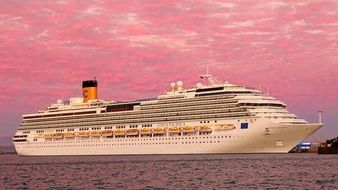 cruise liner on a background of pink sunset