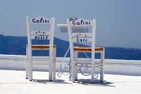 white chairs against the backdrop of a picturesque Greek landscape