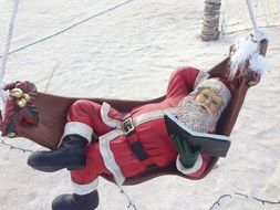 Santa statue reading a book in a hammock on the beach