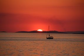 panoramic view of a sailing boat against the backdrop of a romantic sunset