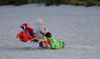 elderly woman sits on a chair on the beach