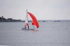 sailboat with a bright red sail