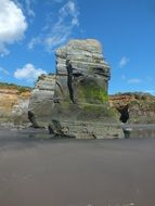 Beautiful Three Sisters rock in moss on the sandy beach in New Plymouth
