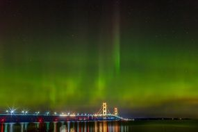 aurora borealis over illuminated bright bridge in michigan
