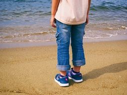 child in blue jeans on a sandy beach